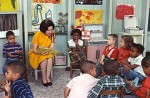 The photograph shows Lady Bird Johnson, the First Lady, reading to children enrolled in Project Head Start at Kemper School in Washington, DC.